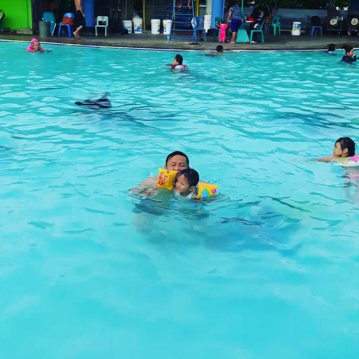 berenang di kolam renang palem